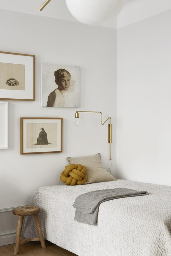Bedroom with serene light neutral grey and putty colors, knot cushion, and gallery wall in Stockholm apartment. #stockholm #smallbedroom #whitebedroom #neutralinterior