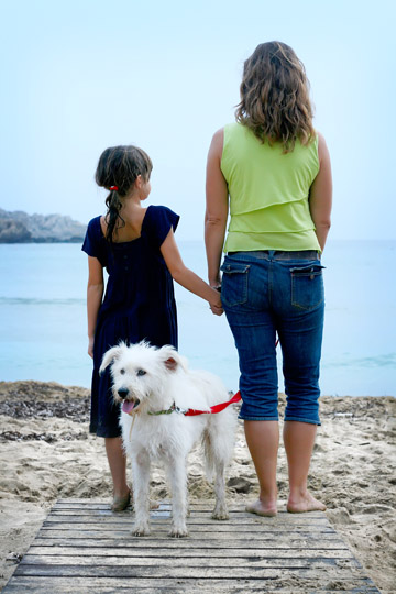 Mother and daughter with dog, standing on sandy beach, Malta