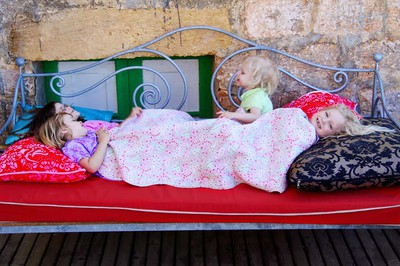 Young kids fooling around outside on a day bed