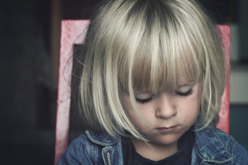 Vintage look picture of a sad little girl