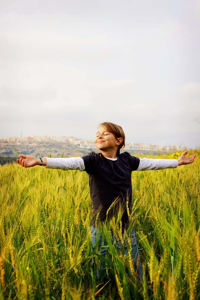 Young girl dancing in a wheat field in Mgarr, Malta